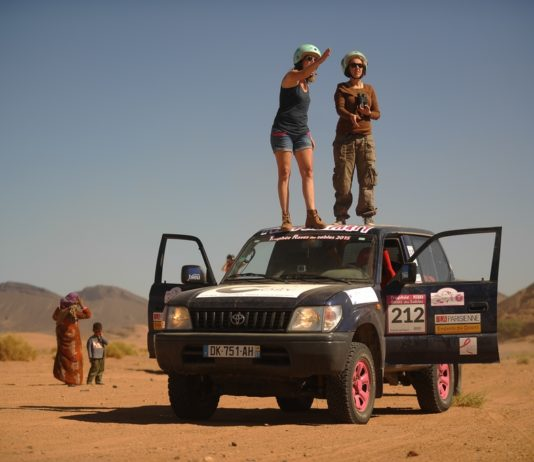 Mujeres compitiendo en el desierto paradas sobre su 4x4